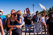 28 JULY 2020 - DES MOINES, IOWA: Supporters of Black Lives Matter stand in the west bound lanes of Grand Ave while they  march up Grand Ave to the Governor's Mansion in Des Moines. About 150 supporters of Black Lives Matter marched from downtown to Des Moines to the Governor's Mansion. They were demanding that Iowa Governor Kim Reynolds restore the voting rights for felons who have completed their sentence. In June, Reynolds met with representatives of Black Lives Matter and promised to sign an executive order to restore voting rights, but she hasn't said anything more about it in six weeks. Iowa is now the only state in the US that permanently strips felons of their voting rights. That means 60,000 people in Iowa can't vote.    PHOTO BY JACK KURTZ