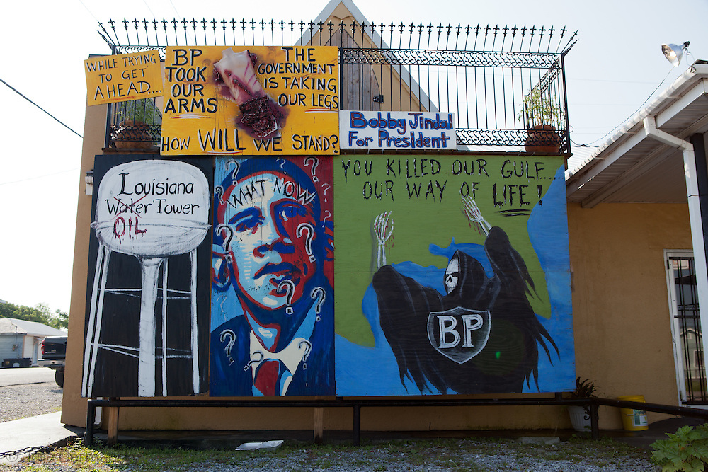 Bobby Pirtre on US Highway 1 in front of a mural he made on his tattoo shop, his response to the BP oil spill.