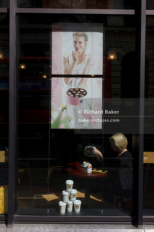 Businesswoman sits in sunlit window beneath poster showing quality chocolates, in Manon Cafe on King William Street in the City of London, the capital's oldest, financial heart.