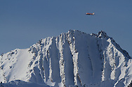 Specially-equipped plane flies over mountain near the international science village of Ny-Alesund on Spitsbergen to research weather and sea ice in the Arctic; Svalbard, Norway.
