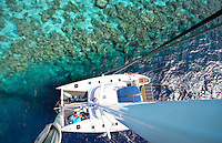 Discovery glides into the lagoon at Namu, Marshall Islands on the Best Odyssey expedition.  Captain Gavin McClurg nudges the boat up near the reef and tows the guests behind and I climb the mast to capture the beauty and color of a place only a handful of people have ever seen.