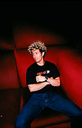DJ Josh Wink sitting on a plush red couch
