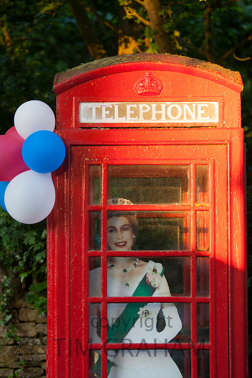 Cutout image of Queen Elizabeth II in phonebox at street party to celebrate the Diamond Jubilee in Swinbrook in the Cotswolds, UK