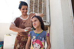 © Licensed to London News Pictures. Hamdaniyah, Iraq. 26/07/2014. Sahira Samir Kamal, an Iraqi Christian refugee from Mosul, brushes her the hair of her daughter, Dilar (9), after being resupplied with fresh drinking water by Kurdish Zeravani soldiers at the partially built home they share with 15 other family members in Hamdaniyah, Iraq. Sahira and her family left Mosul on Friday the 18th of July when Islamic State fighters issued an ultimatum to the city's Christian community. When the family left they were forced to pay a tax for their car, their son (19) was threatened at knifepoint to ensure they handed over all of their possessions including family photographs.<br /> <br /> Having taken over Mosul Iraq's second largest city in June 2014, fighter of the Islamic State (formerly known as ISIS) have systematically expelled the cities Christian population. Despite having been present in the city for more than 1600 years, Christians in the city were given just days to either convert to Islam, pay a tax for being Christian or leave; many of those that left were also robbed at gunpoint as they passed through Islamic State checkpoints.. Photo credit : Matt Cetti-Roberts/LNP