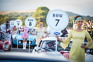 Women dressed in 1960's vintage clothing stand next to classic vehicles ahead of the Kinrara Trophy race at the Goodwood Revival in Chichester, England   Friday, Sept. 9, 2016 The historic motor racing festival celebrates the mid-20th-century golden era of the racing circuit and recreates the atmosphere from the 1950s and 1960s.(Elizabeth Dalziel)