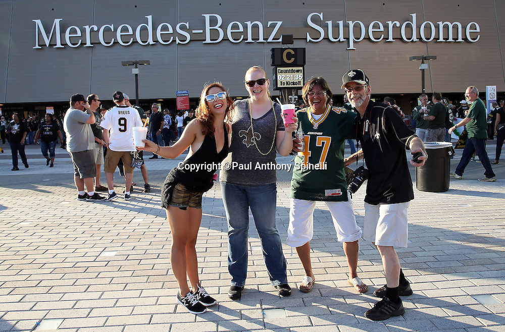 Fans pose for a photo in front of the Mercedes-Benz Superdome before the NFL week 8 regular season football game against the Green Bay Packers on Sunday, Oct. 26, 2014 in New Orleans. The Saints won the game 44-23. ©Paul Anthony Spinelli