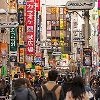 Narrow, busy sign-covered street near Shibuya Crossing in Tokyo, Japan.