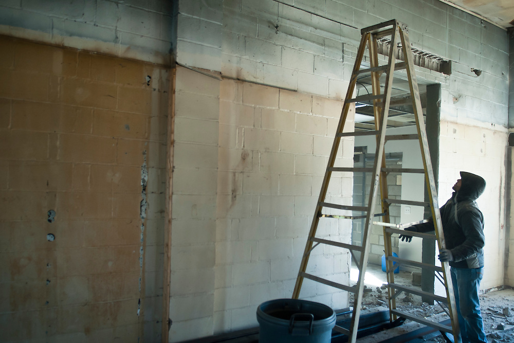 Lathan Goumas | MLive.com..February 20, 2012 - Construction worker Sonny Meyo, of Farmington Hills, moves a ladder while renovating a building next to the Goodrich Plaza into a pharmacy at 8191 S. State Rd in Goodrich on Monday.