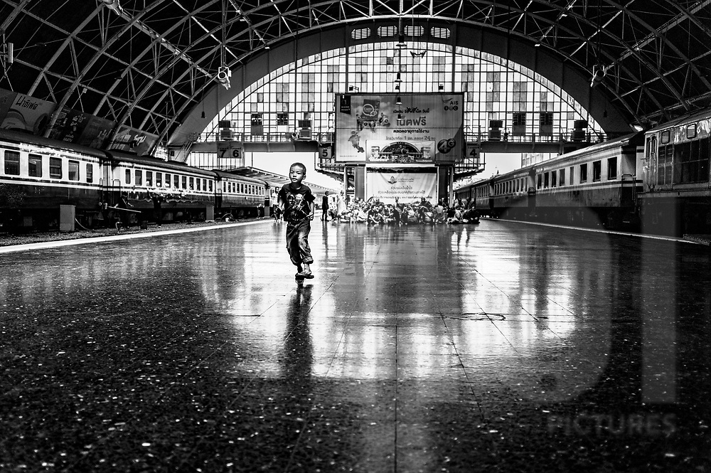 A young boy runs along a train platform in Hua Lamphong Station, Bangkok, Thailand, Southeast Asia