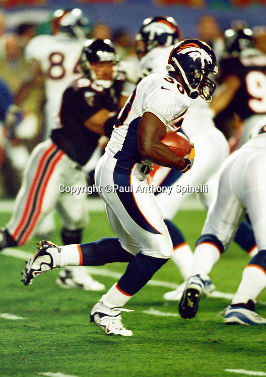 Denver Broncos running back Terrell Davis (30) runs the ball during the NFL Super Bowl XXXIII football game against the Atlanta Falcons on Jan. 31, 1999 in Miami. The Beroncos won the game 34-19. (©Paul Anthony Spinelli)