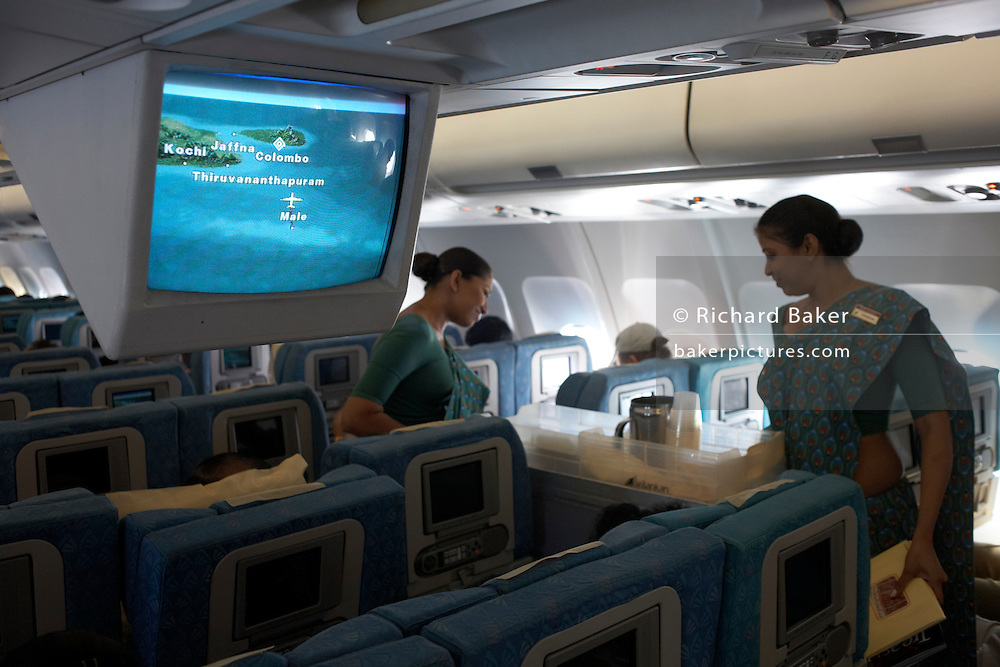 Sri Lankan Airlines cabin crew serve drinks to economy class passengers between the Maldives and Colombo