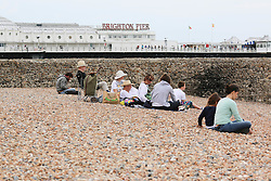 © Licensed to London News Pictures. 08/07/2014. Brighton, UK. A family having lunch on Brighton beach.Despite temperatures in the next weeks are expected to soar to 86F around the UK with the South Coast predicted to hit record according to the MET the weather is very much cloudy today July 9th. Photo credit : Hugo Michiels/LNP