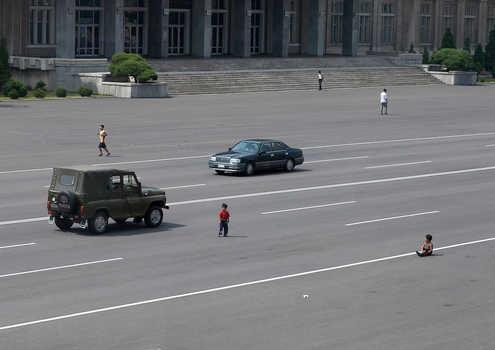Street scene in Pyongyang, North Korea. As cars have become more widespread in Pyongyang, the peasants are still getting accustomed to seeing them. Kids play in the middle of the main avenues just like before when there were no cars in sight.