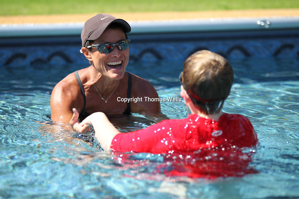 Gina Fremont works with Noah Massengill into her pool for his swimming lesson.