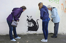 """© Licensed to London News Pictures. 31/10/2015. Folkestone, UK.  Members of the public look at a new artwork by the artist BANKSY, next to the location of a BANKSY piece that was removed. The Artwork pokes fun at the removal of the last piece which was called """"Art Buff"""", which was of an old lady, and says """"IF FOUND PLEASE CONTACT ALASTAIR. Alastair Upton is the Chief Executive of the Creative Foundation who as called for the picture to be returned to the town. Photo credit:Grant Falvey/LNP"""