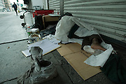 Ukele' sleeps with one sock, as he and other homeless people take refuge on the street in the early morning sunlight on Los Angeles St. in Downtown Los Angeles, Ca. April 25, 2006.