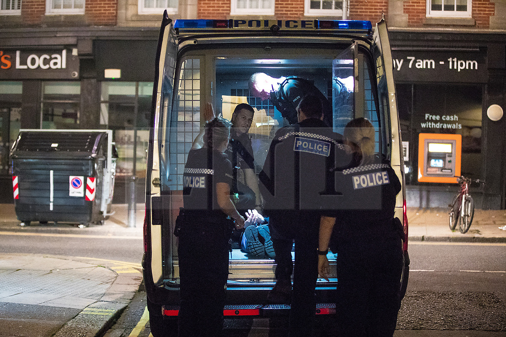 © Licensed to London News Pictures . 26/09/2017. Brighton, UK. Police detain , handcuff , bind the legs and put a hood over the head of a man outside a branch of Subway , before carrying him in to the back of a police van , after a fight in Steine Gardens in the Kemptown area of the city . Revellers at the end of a night out in Brighton during Freshers week , when university students traditionally enjoy the bars and clubs during their first nights out in a new city . Photo credit: Joel Goodman/LNP