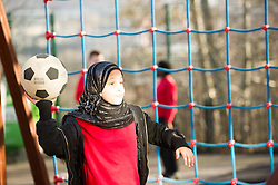 A young Asian girl playing with a football in a playground
