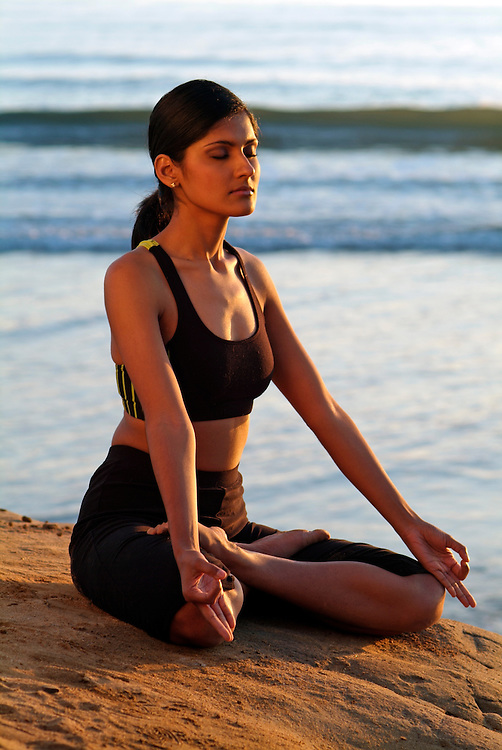 Wellness image of young woman meditating on cliff overlooking ocean at sunset