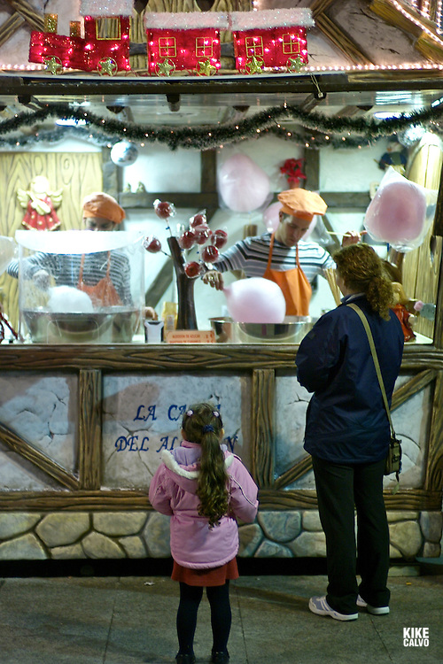 Christmas arrives at The Basilica-Cathedral of Our Lady of the Pillar in the city of Zaragoza, Cotton, candy and sweet apple store.A happy girl waits for her cotton candy.