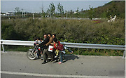 Solved! How A Family Of Eight Can Travel From A To B... On Just Two Wheels<br /> <br /> China - How does a large family commute anywhere if they have no car and little money? As this picture proves, there are no problems, only solutions. What appears to be an entire family of eight have all piled cheerfully on to one motorcycle. The three children, two men, two women and a baby are clinging to one another tightly, their hair blowing in the breeze - as they are, of course, compounding their danger by riding without helmets.<br /> Their lives appear to be in the hands of one of the men - clad in a dark purple shirt, he is the driver. His control of the motorbike is compromised by the three children crammed on the saddle in front of him however. One hopes they only have to travel in a straight line, as he will find it very difficult to turn the bike with the three children there. Of course, the weight he is carrying on the back of the motorbike will not help either.  To go around corners on a motorbike, the driver must lean into the turn. That is always more difficult to do when carrying a passenger - if the passenger does not lean with the bike also, or if they lean too little or too much, the driver could lose control.  Unless you are an experienced rider, that's difficult enough to manage with one passenger. With seven, it must be just about impossible. The driver will also find stopping difficult. When you stop on a motorbike, you have to put your feet down to balance the bike and keep it upright.  But the weight of seven other people on the bike will be too much for the driver to support on his own, so the adults will have to put their feet down also at any stoplight. They will all have to then make sure they lift their feet in tandem as the driver starts again - if he tries to accelerate while one person still has their feet on the ground, the entire operation could fall apart. Photo Shows: It's hard to tell where the family are - though, fortunately for them, th
