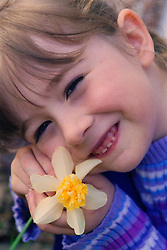 Portrait of young girl holding flower smiling,