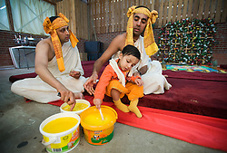 "© under license to London News pictures.  06/11/2010.A small boy mixing ghee with his father, a Hindu Priest. Celebrations for Diwali, the Hindu new year, at Gokul Centre for Cow Protection and Working Oxen in Aldenham near Watford, Hertfordshire today (Sat). The centre, which was originally donated by George Harrison, is unique in the western world producing ""Ahimsa Milk"" at a cost of £3 per litre without harm to any living being. The Centre is part of Bhaktivedanta Manor, a Hindu place of worship."