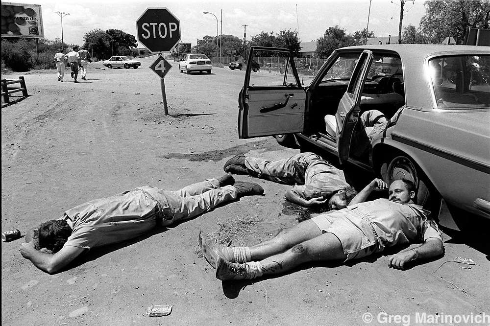 IPMG0048 South Africa, Mafekeng 1994..Journalists run in distance after Bophuthatswana army members executed two of the three far right wing Afrikaner Resistance Movement mebers during an attempted AWB coup in the homeland March 123, 1994..Photograph by Greg Marinovich/South Photographs