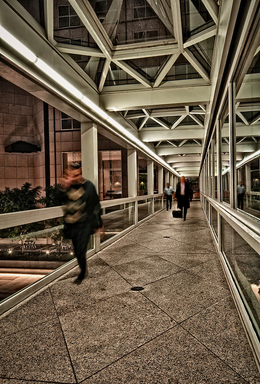 People rushing out of work in a modern building at night.