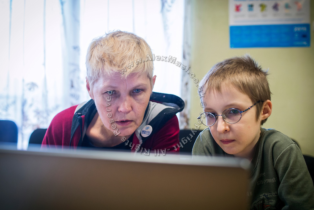 Using a computer, Marina Rassokha, 50, of 'Ukrainian Frontiers', is reviewing some video made by Yaroslav, 10, while inside a community meeting place in support of internally displaced persons. (IDPs) Yeroslav is taking part to the UNICEF-sponsored One Minute Junior project for internally displaced persons (IDPs), carried out by the local NGO 'Ukrainian Frontiers' in the city of Kharkiv, the country's second-largest, in the east. The conflict between Ukrainian army and Russia-backed separatists nearby, in the Donbass region, have left more than 10000 dead since April 2014, including over 1000 since the shaky Minsk II ceasefire came into effect in February 2015. The approximate number of people displaced by the conflict is 1.4 million as of August 2015. Yeroslav's mother, Olga, is also a participant to a different project of 'Ukrainian Frontiers', called 'Self-Employment', first as a beneficiary, and now as a paid hotline coordinator for people seeking jobs and formation courses.