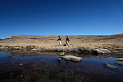 Walkers hike along the Tugela river at the top of the Amphitheatre in the Drakensberg mountains. Royal Natal National Park. Kwa-Zulu Natal, South Africa..© Zute Lightfoot.Zute & Demelza Lightfoot.www.lightfootphoto.com