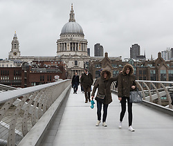 © Licensed to London News Pictures. 29/05/2015. London, UK. Two women wearing winter coats with hoods cross the Millennium Bridge during wet and overcast weather in London today. Today is the first day of British Summer Time (BST).  Photo credit : Vickie Flores/LNP