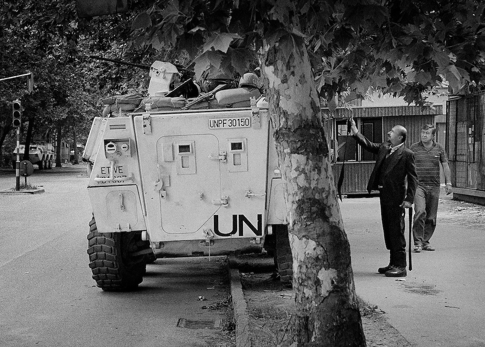 Mostar, Bosnia, 1993.<br /> <br /> Mostar civilian attempting to sell ties to Spanish UN soldiers.