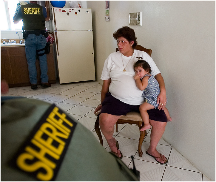 Michael Stenerson / Staff Photographer.A woman holds a small child as authorities search her residence in Adelanto during a search warrant sweep on Thursday. The woman's identity could not be confirmed due to a wide array of fake ID's and social security cards found at the residence.