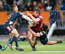 Crusaders' George Bridge, centre, is tackled by Highlanders' Aaron Smith, left, and Dillon Hunt in the Super Rugby match, Forsyth Barr Stadium, Dunedin, New Zealand, Saturday, March 17, 2018. Credit:SNPA / Adam Binns ** NO ARCHIVING**
