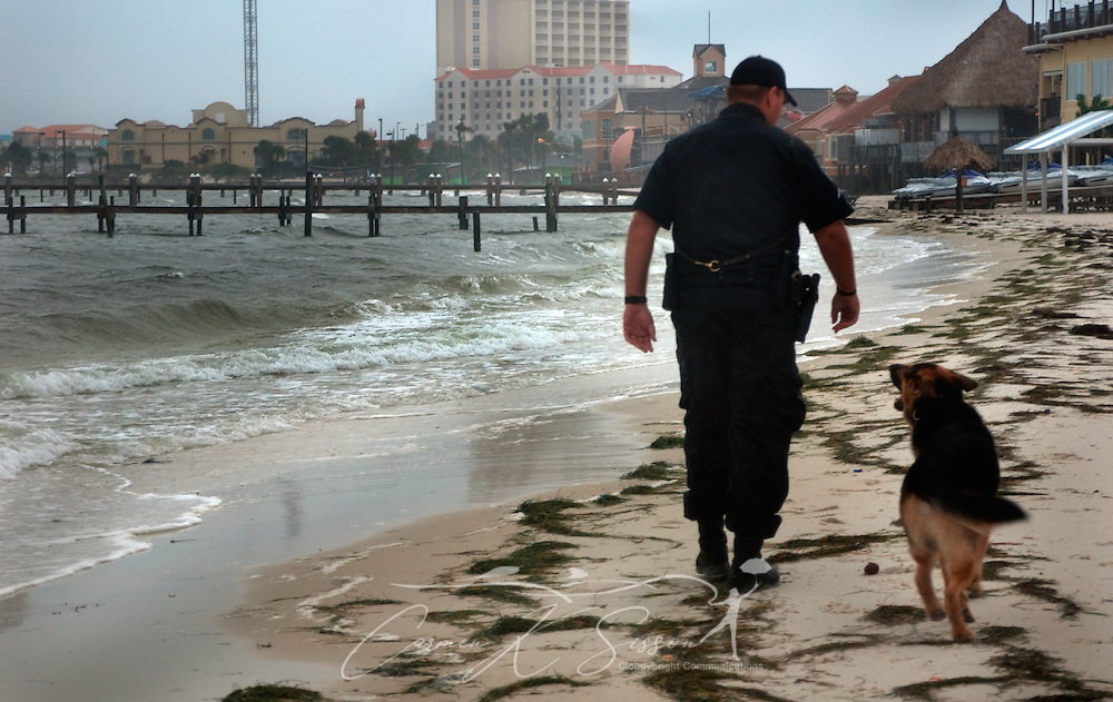 Escambia County Deputy Sheriff Patrick Frazier walks along Pensacola Beach with his dog, Nido, Nov. 9, 2009 in Pensacola, Fla. Residents along the coast spent Monday making preparations for the arrival of Hurricane Ida, which was downgraded to a tropical storm before landfall. (Photo by Carmen K.Sisson/Cloudybright)