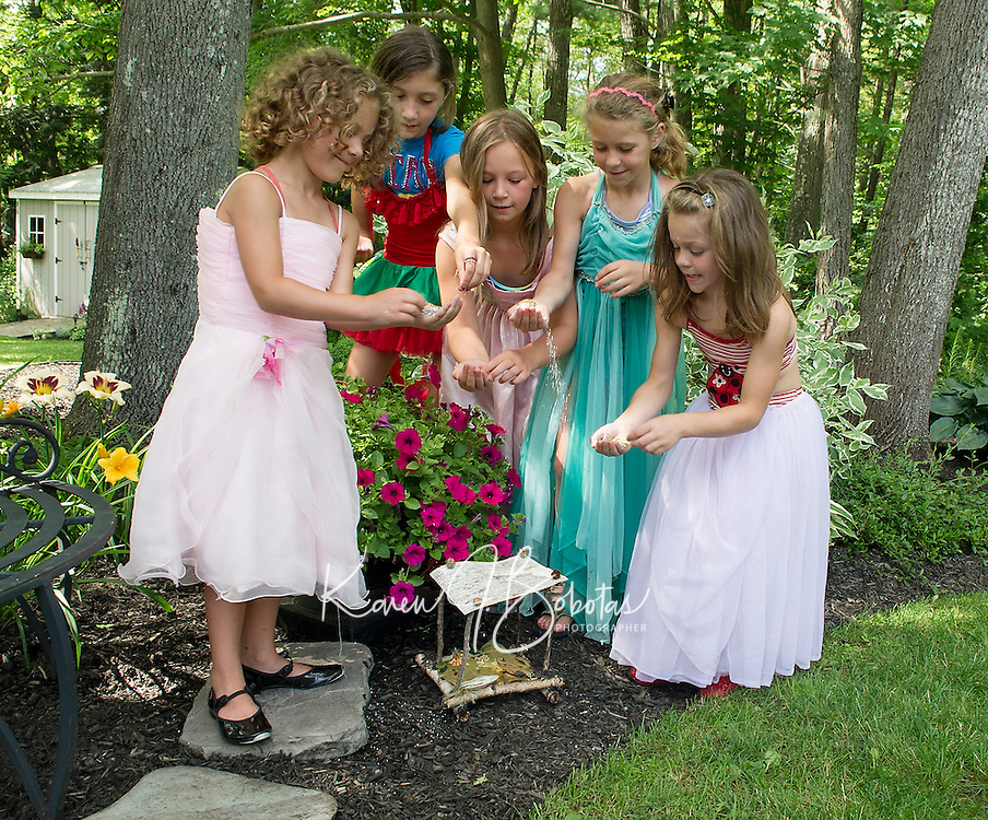 """""""Fairies"""" from the Boys and Girls Club add sparkle to their fairy houses placed among the gardens at Robert King and Elaine Muller's home prior to Opechee Garden Club's """"Awesome Blossoms"""" Tour on Saturday.  (Karen Bobotas/for the Laconia Daily Sun)"""
