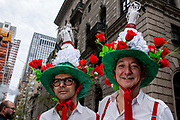 """New York, NY - April 16, 2017. Two men wear hats topped in white doves, with signs reading """"Peace in the World"""",  at New York's annual Easter Bonnet Parade and Festival on Fifth Avenue."""