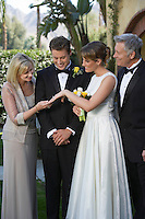 Bride showing ring to mother, groom and father looking on
