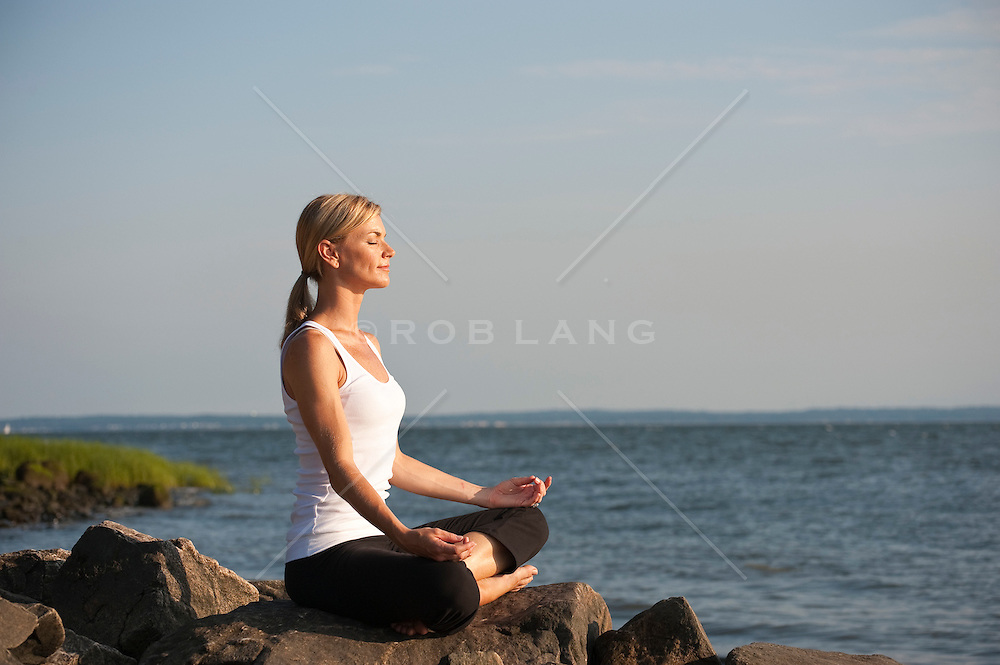 Young woman meditating on the barrier rocks on the Long Island Sound