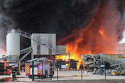 "© Licensed to London News Pictures . 15/03/2015 . Salford , UK . Fire crews at the scene . Roads are closed and people have been evacuated as a large fire burns at a unit within "" Junction Eco-Park "" in Clifton , Greater Manchester , this evening (Sunday 15th March 2015) . The smoke and flames can be seen for many miles . Forty fire fighters are at the scene working to control the blaze . Photo credit : LNP"