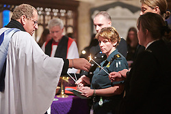 © Licensed to London News Pictures.  17/11/2013. THAME, UK. Canon David Wilbraham, Force Chaplain with the Thames Valley Police lights a candle using a flame taken from the paschal candle during the annual Road Deaths Memorial Service held in St Marys Church, Thame.  78 people were killed in traffic accidents in the Thames Valley Police area last year.  Photo credit: Cliff Hide/LNP