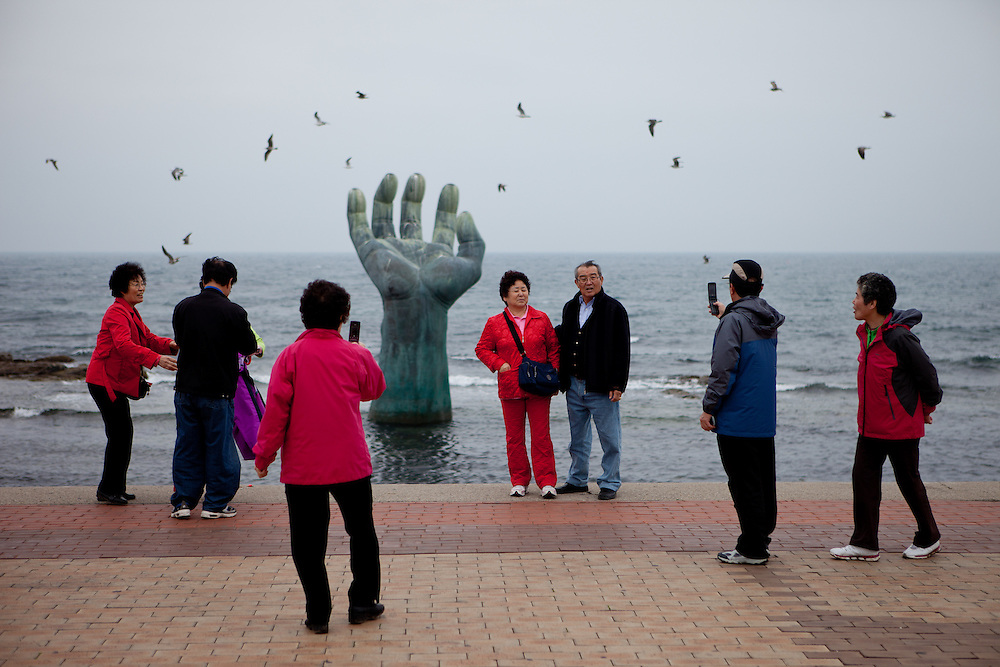 """Visitors photographing each other at the """"Hand of Harmony"""" located at Homigot Beach close to Pohang city at the South Korean East coast. South Korea, Republic of Korea, KOR, 20.04.2010"""