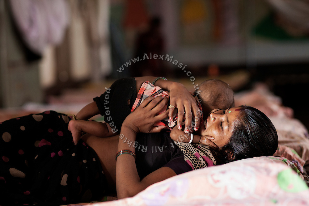 A mother is holding her malnourished child while laying on their bed inside a feeding centre run by UNICEF in the town Shivpuri, Madhya Pradesh, India.