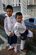 Moslem boys  wait to attend friday prayers at the Omar Ali Saifuddien Mosque..Bandar Seri Begawan, Brunei.