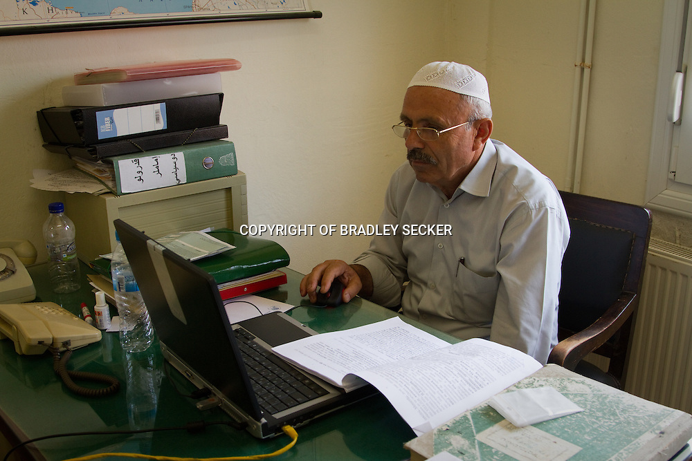 Mufti Sherife Damadoglou working in his office in the border town of Didymothicho, Evros, Greece. The Mufti is responsible for the traditional Islamic burial of migrants who's bodies have been recovered in the border region, and died crossing.