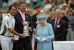 Queen Elizabeth II presents a trophy to La Inidiana's player Michael Bickford, left, at the Cartier Trophy at the Guards Polo Club, Windsor Great Park, Surrey.
