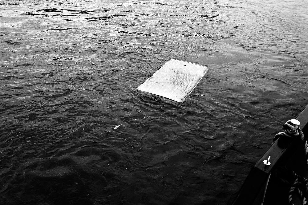 Un matelas  otte le long de L'Auxerrois, une péniche chargée de containers.