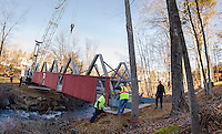 Mark Roberts operates the crane with Jim Fortin, Woody Fogg, Ron Mitchell and Chris Clairmont ready to set the bridge spanning the Tioga River in Belmont Village Monday afternoon.  (Karen Bobotas/for the Laconia Daily Sun)