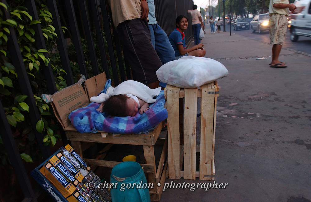 ASUNCION, PARAGUAY. A baby sleeps in a bed made of cardboard and a fruit crate in Asuncion, Paraguay on Wednesday, March 15, 2006. Hundreds of street children, some as young as 4 years old and their parents, work the diesel fumed streets of the capital city by squeegeeing windshields, panhandling and selling various items to drivers.